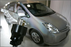 A Toyota employee holds up the three-prong plug during the unveiling of a plug-in Prius.