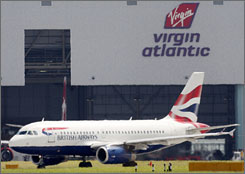 A British Airways plane is seen in front of a Virgin Atlantic hangar at London's Heathrow Airport on Wednesday.