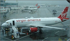 Workers at JFK Airport in New York ready an Airbus for Virgin America's first flight in soggy weather Wednesday.