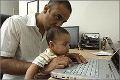 Raj Nijjer, 29, who oversees a staff of four software test engineers, works on his laptop with his 8-month-old son, Kabir, on his lap at their home in North Scottsdale, Ariz.