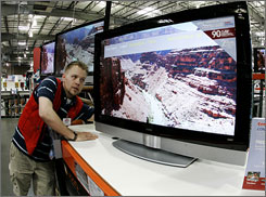 Chris Wise adjusts a high-definition set at a Costco in Tacoma, Wash.
