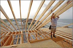 Tony Cook steadies rafters on a house on Dauphin Island, Ala., that's being rebuilt after Hurricane Katrina destroyed it.
