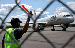 A worker directs a jet to its gate at Bradley Airport in Windsor Locks, Conn. Most of the biggest ailrines are boosting their workforces.