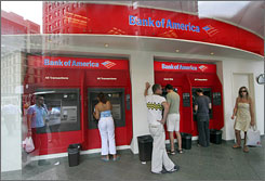 Customers use automated teller machines at a Manhattan branch of Bank of America. The bank is now charging $3 for non-customers who make withdrawals at most ATMs.