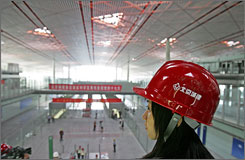 A worker wearing a safety helmet looks on during a media preview of the new terminal at Beijing's Capital International Airport.