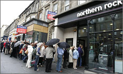 Customers line up outside an Edinburgh branch of Northern Rock bank on Saturday to withdraw their savings. The bank had asked for an emergency loan from the Bank of England.