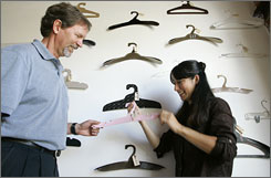 Dominican University professor John Stayton reviews recyclable clothes-hanger designs with MBA student Miya Kitahara.