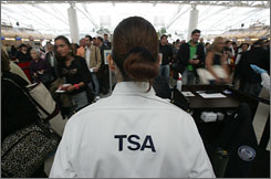 A Transportation Security Administration screener watches passengers at New York's JFK International Airport. Screeners are being taught ways to spot suspicious behavior in crowds.