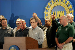 Surrounded by GM and United Auto Workers negotiators, UAW President Ron Gettelfinger announces a tentative agreement early Wednesday morning.