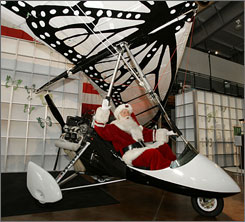 Brady White as Santa checks out the papalotzin Ultralight, available in the Neiman Marcus Christmas Book. The Ultralight was used by Vico Gutierrez in a documentary on the Monarch Butterfly.