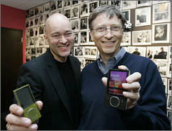 Micosoft Chairman Bill Gates, right, and Vice President J Allard hold new Zune portable media players announced Tuesday.