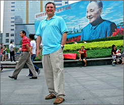 Mark Giorgini, near a billboard of Deng Xiaoping in Shenzhen, China, consults for firms wanting to do business in China.