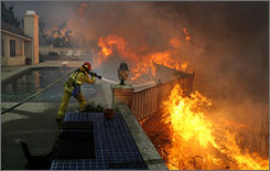 Firefighter Jason Falarski battles to save a house Monday in Poway, Calif.