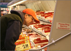 Jim Rekas looks over meat selections at a Giant store in Herndon, Va. The grocery chain has dropped carbon monoxide-infused packaging.