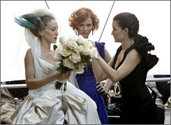 "Sarah Jessica Parker, left, Cynthia Nixon and Kristin Davis film a scene on the set of ""Sex and the City: The Movie"" in New York last month. Fans are eagerly anticipating the film."