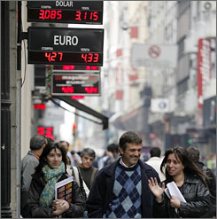 Pedestrians walk under a display of the dollar-peso exchange rate in Beunos AIres in July.