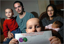 Fabian Reyes, 5, holds a foreclosure notice his family received at their home in Machesney park, Ill. The family includes (from left) Mason, 3, dad Steve, 26, mom Dawn, 27, and Cerenaty, 2 weeks. The stickers were the kids' own personal touch.