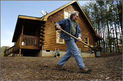 Bob Singer, of Golden Valley Getaways, adds dirt to insulate around a well cover at the R&R Log Cabin in preparation for winter in Yellowtop Mountain Estates near Golden Valley, N.C., on Nov. 8.