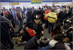 JetBlue passengers wait at New York's Kennedy Airport on Feb. 15, after passngers were stuck on grounded planes for hours.