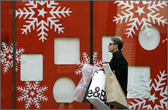 A San Francisco shopper walks past a Macy's window. Tightening personal budgets may curtail some Christmas spending this year.