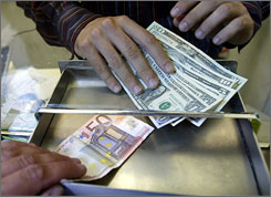 A worker changes euros and dollars at an exchange kiosk in Italy.