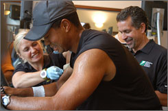 Tiger Woods, front, undergoes scientific sweat analysis testing with scientists Beth Stover and Bob Murray of the Gatorade Sports Science Institute.
