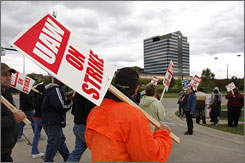 UAW members picket Chrysler in Auburn Hills, Mich., in October. Experts disagree on whether the union is better or worse off with the new contracts.