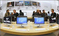 Customers browse iMacs at an Apple Store in Salt Lake City. Macs are generally more expensive than Windows PCs, but Mac lovers say they're worth it.