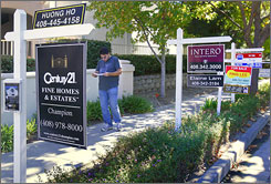 Passerby John Malone reads about one of many homes for sale on a San Jose, Calif., street.