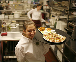 Margit Chamberlain, a freshman at Cornell's School of Hotel Administration, works at the Taverna Banfi Restaurant in the school-run Statler Hotel.