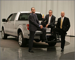 Ford's Todd Eckert, left, Pat Schiavone, center, and Matt O'Leary show off a handle and step to help people get into and out of the F-150's truck bed.