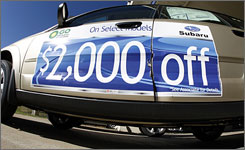 Dealership signs like this on a 2008 Subaru Outback will be less common this year as carmakers are likely to scale back incentive and rebate offers.
