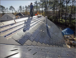 A worker installs solar-paneled shingles on a home in Raleigh, N.C., in 2006. Solar-power stocks made strong gains in 2007 but are struggling this year.