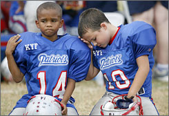 Tiny football players react after losing the coin toss in a photo by Diana Porter of Houston that won the feature category of Canon's amateur photo contest.
