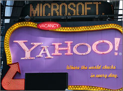 A Times Square news ticker flashes a headline about Microsoft above a billboard for Yahoo.