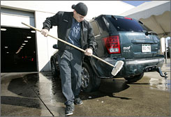 Pro Chrysler Jeep Denver employee Damian Thomas washes a Jeep Grand Cherokee in Thornton, Colo.