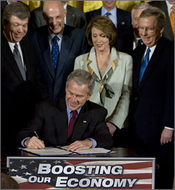 President Bush signs the economic stimulus bill Wednesday in the White House, as lawmakers including House Speaker Nancy Pelosi look on.