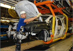 Subaru's strict recycling program requires the cooperation of workers such as Rick Cordray, who tosses a small plastic cap into a recycling bin.