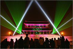 A Beijing crowd watches a laser show, part of the extended celebrations of the Chinese new year, earlier this month by the city's Yongdingmen Gate.