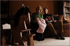 Kelly Jerry, left, and Chris Jerry hold daughter Emily's blanket and photograph, her rocking horse in the foreground. Emily died from a medical mistake.