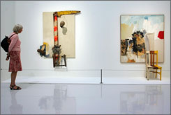 A woman looks at Pilgrim, left, and Aen Floga' pieces by artist Robert Rauschenberg in 2006 at an exhibition in Paris.