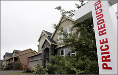 "As home prices fall, more sellers are putting out ""price reduced"" signs like this one in a subdivision in Happy Valley, Ore."