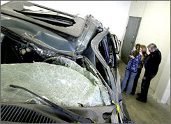 Michelle Moody, left, Veronica Moody, center, and Kevin Moody in a warehouse by the Ford SUV that rolled over in a 2003 accident, killing Tyler, 18.