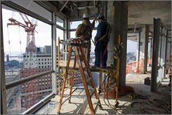 Tommy Holbrook, left, and Herman Rodriguez work on the W hotel going up in Hoboken, N.J. The 26-story hotel overlooks the New York City skyline.