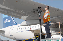 Adam Ris refuels a JetBlue aircraft in Long Beach, Calif., on March 14. High fuel costs have forced JetBlue and other airlines to sell some planes.