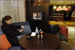 Shiva Barbosa of London checks her messages in the lobby of Marriott's Courtyard Fairfax Fair Oaks in Fairfax, Va. Her booth has its own television.