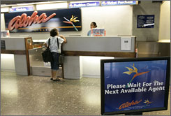 A passenger checks in at the Aloha Airlines counter at Honolulu International on March 30. Aloha is ending flights as it enters bankruptcy protection.