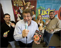 Roger Shiffman, front, with his High School Musical karaoke microphone and ESPN basketball game. His backup singers, from left: Marc Rosenberg, Patty Jackson and David Scher.