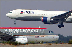 A Northwest Airlines jet taxis as a Delta plane lands in Atlanta in 2005. The merger news comes a year after both airlines emerged from Chapter 11.