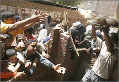 People demand bread northeast of Cairo on March 29, before the government boosted bread subsidies and deployed troops to help distribute loaves.